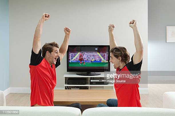 Two young men wearing football shirts watching football on television