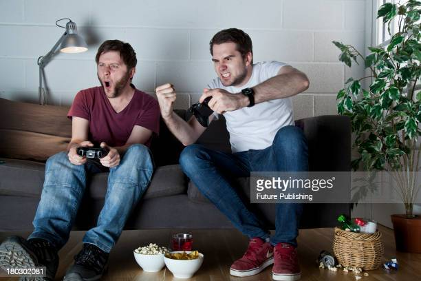Two young men with angry expressions playing Sony PlayStation 3 video games on a sofa taken on July 9 2013