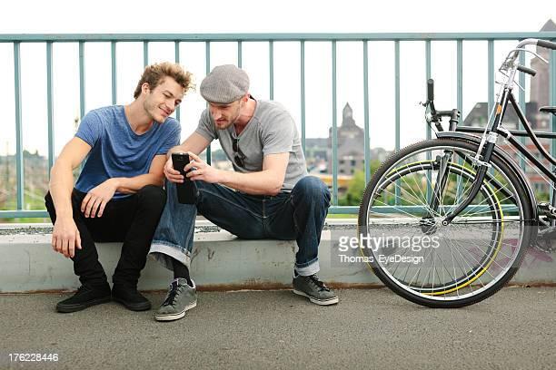 Zwei junge Männer mit Fahrrädern und Handy