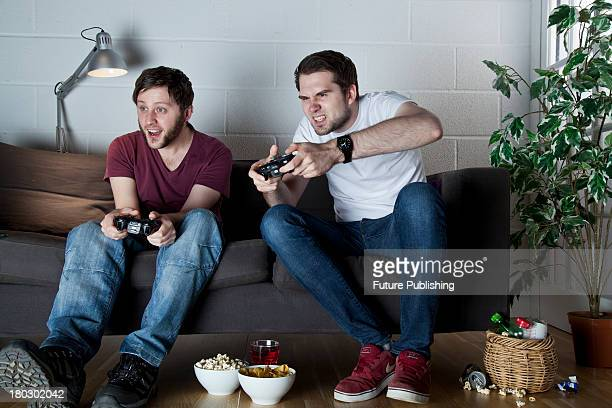 Two young men with cheerful and angry expressions playing Sony PlayStation 3 video games on a sofa taken on July 9 2013