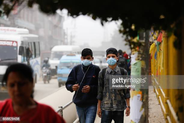 Two young men with face masks walk in a dusty road in Kathmandu Nepal on March 28 2017 Construction and road expansion works increase in number of...