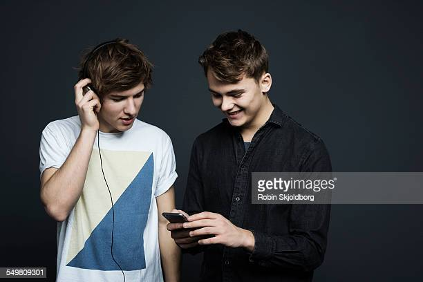 Two young men with headphones and Iphone