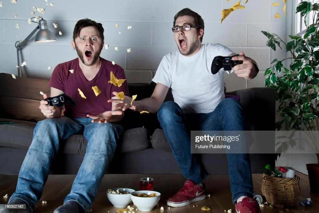 Two young men with shocked expressions playing Sony PlayStation 3 video games on a sofa as snacks fly through the air around them, taken on July 9, 2013.