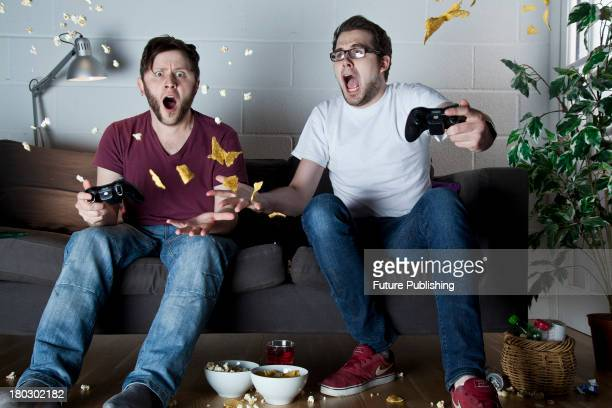 Two young men with shocked expressions playing Sony PlayStation 3 video games on a sofa as snacks fly through the air around them taken on July 9 2013