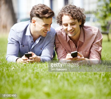 Two young men with smart phones in urban park : Stock Photo