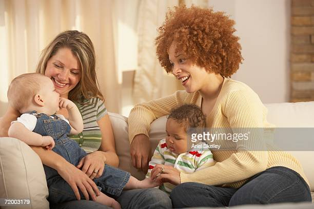 Two young mothers with babies on sofa