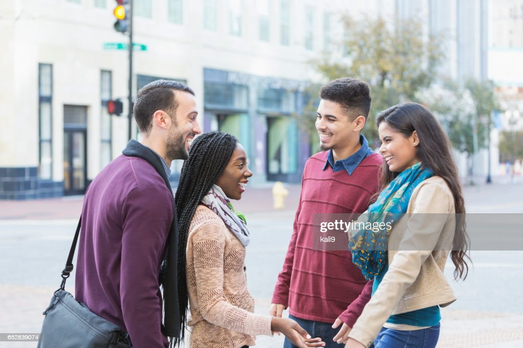 Two young multi-ethnic couples talking on city street : Stock Photo