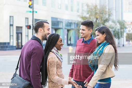 Two young multi-ethnic couples talking on city street : Stock-Foto