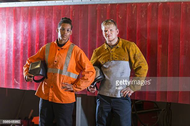 Two young multi-ethnic workers with welding masks