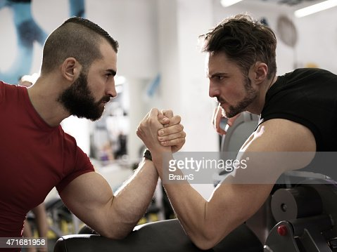 Two young muscular build men arm wrestling in a gym.