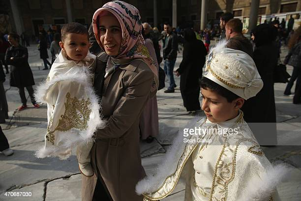 Two young Muslim boys wearing regal outfits that indicate today is their circumcision ceremony walk with family members through the main inner...