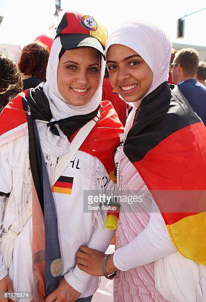 Two young Muslim girls wearing headscarves and German flags await the German national football team at the Fan Mile in front of the Brandenburg Gate...