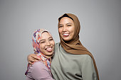 Two Young Muslim girls wearing hijab sticking out tongue and smiling in front of camera isolated on grey