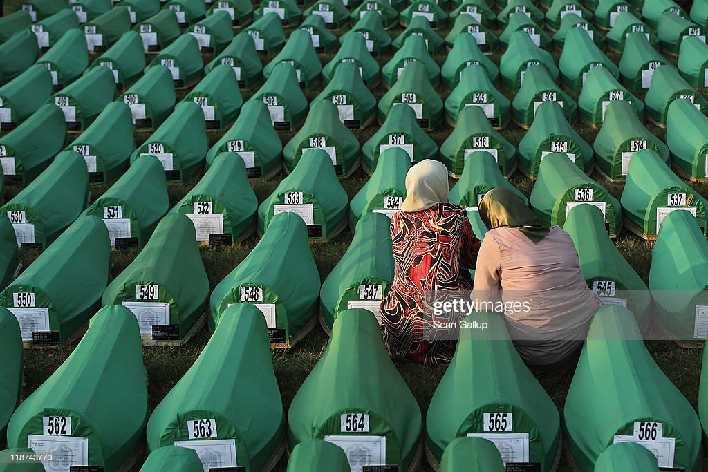 Two young Muslim women mourn over a coffin among 613 coffins of victims of the 1995 Srebrenica massacre laid out on a lawn at the Potocari cemetery...