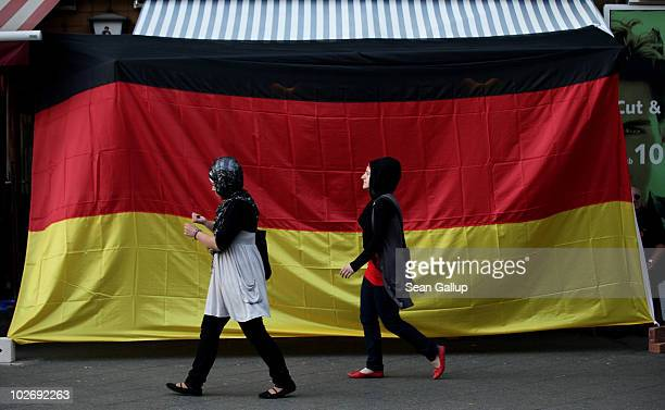 Two young Muslim women walk by a pub draped in a German flag in the Arab and Turkishheavy neighborhood of Neukoelln during the FIFA 2010 World Cup...