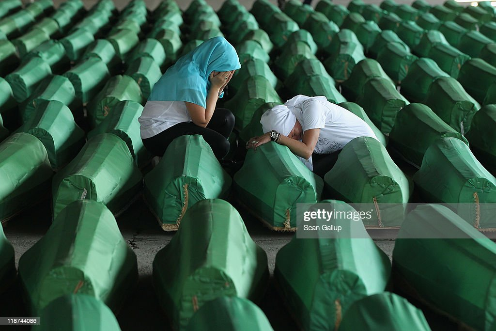 Two young Muslim women weep over one of 613 coffins of victims of the 1995 Srebrenica massacre in a hall at the Potocari cemetery and memorial near Srebrenica on July 10, 2011 in Potocari, Bosnia and Herzegovina. The newly-identified remains of the 613 victims are scheuled to be buried in a ceremony to be held on July 11, the 16th anniversary of the massacre. At least 8,3000 Bosnian Muslim men and boys who had sought safe heaven at the U.N.-protected enclave at Srebrenica were killed by members of the Bosnian Serb army under the leadership of General Ratko Mladic, who is currently facing charges of war crimes in The Hague, during the Bosnian war in 1995. A Dutch court recently found the Dutch government responsible for the deaths of three of the victims when Dutch U.N. peacekeepers handed the three men, who had been working on the Dutch base in Srebrenica, over to Serbian soldiers.