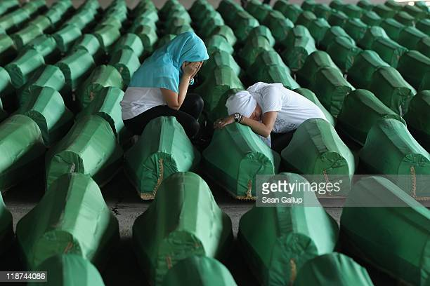 Two young Muslim women weep over one of 613 coffins of victims of the 1995 Srebrenica massacre in a hall at the Potocari cemetery and memorial near...