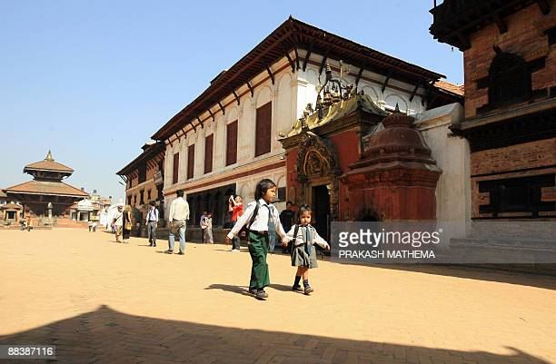 Two young Nepalese students pass through the Bhaktapur Durbar Square in Bhakatpur some of 12 kilometers southeast of Kathmandu on June 10 2009...