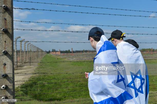 Two young participants touch a barbed wire fence during the annual March of the Living inside the former German Nazi Death Camp AuschwitzBirkenau...