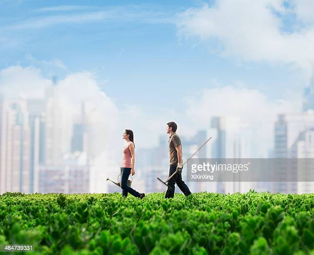 Two young people carrying gardening equipment walking across a green field with plants, cityscape in the background