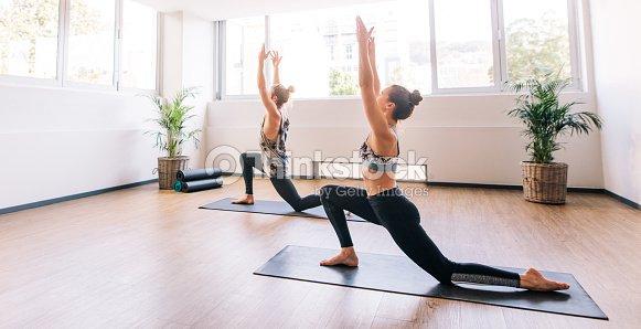 Dos jóvenes haciendo yoga en el interior   Foto de stock 07ee3e1333df