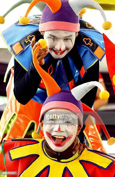 Two young people dressed as jokers entertain children outside a church after a special prayer as a part of Christmas celebrations in Jakarta 25...