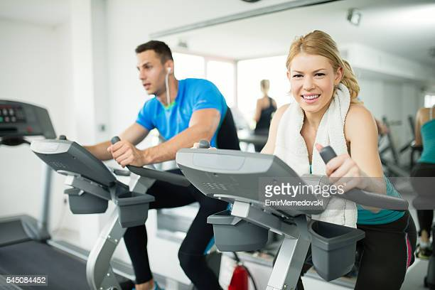 Two young people spinning on exercise bike at gym.