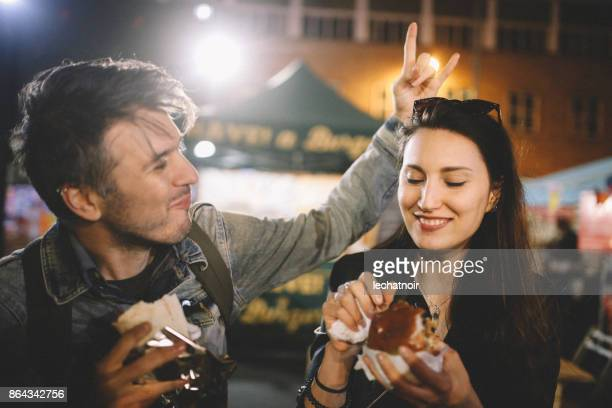 Two young people having fun eating street food in London at night
