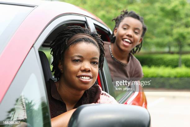 Two young people leaning out of the windows of a car