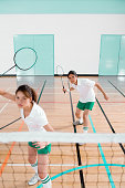 Two young people playing badminton