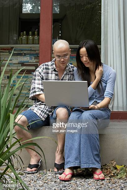 Two young people using a laptop.