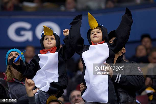 Two young Pittsburgh Penguins fans dressed as Penguins cheers for their team during the third period of their NHL hockey game against the Toronto...
