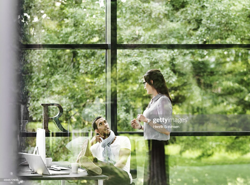 Two young professionals talking : Stock Photo