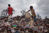 Two young scavenger boys search for recyclable material between tons of trash in the Anlong Pi landfill on June 11 2014 in Siem Reap Cambodia Dozens...