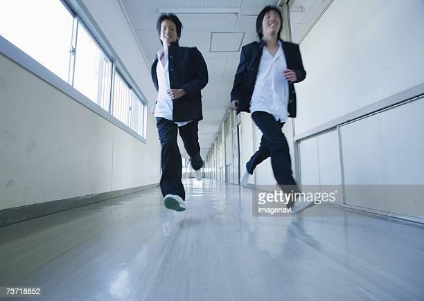 Two young schoolboys running in corridor