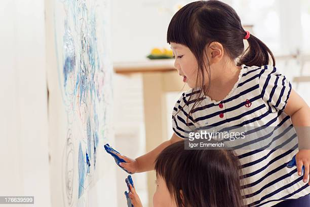 Two young sister making handprint painting