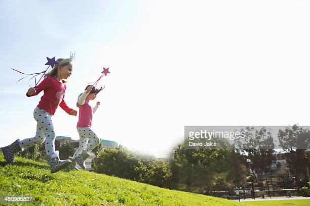 Two young sisters dressed up as fairies running down hill