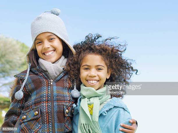 Two young sisters hugging in winter