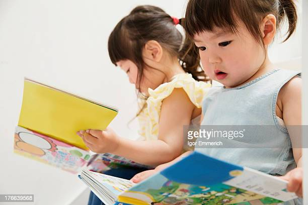 Two young sisters looking at picture books