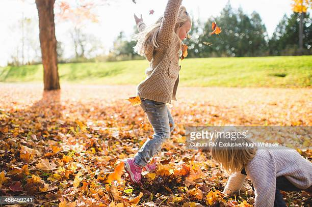 Two young sisters playing with autumn leaves in park