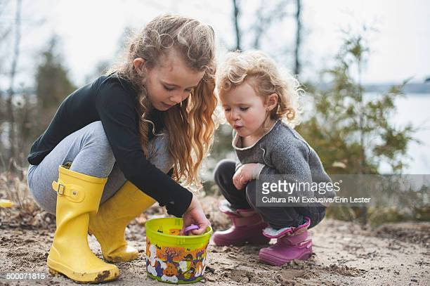 Two young sisters playing with sand and bucket by lake