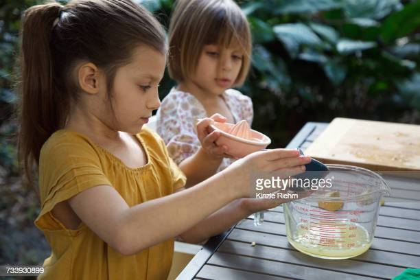 Two young sisters pouring lemon juice for lemonade at garden table