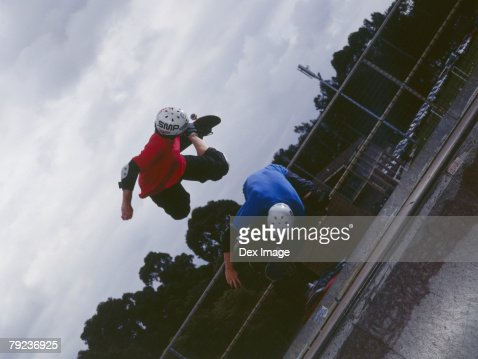 Two young skateboarders in mid air : Stock Photo