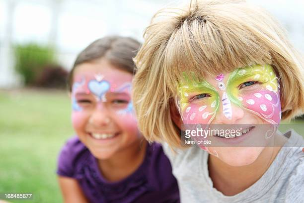 Two young smiling girls with their faces painted