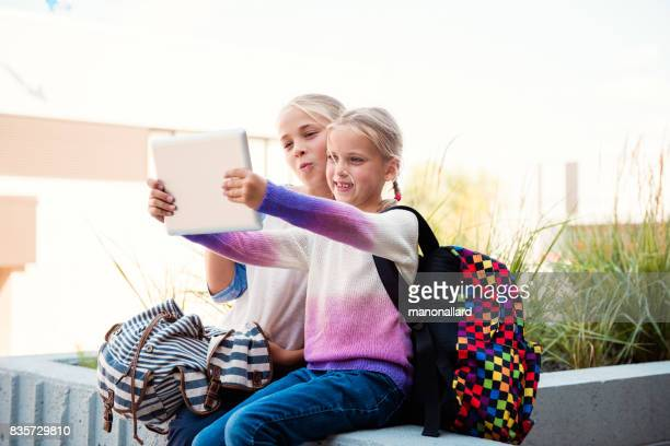 Two young students girls back to school making selfies on digital tablet at the entrance of the school