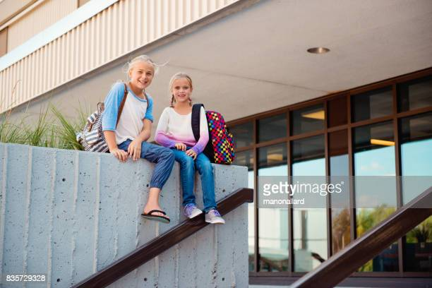 Two young students girls back to school sitting at the entrance of the school