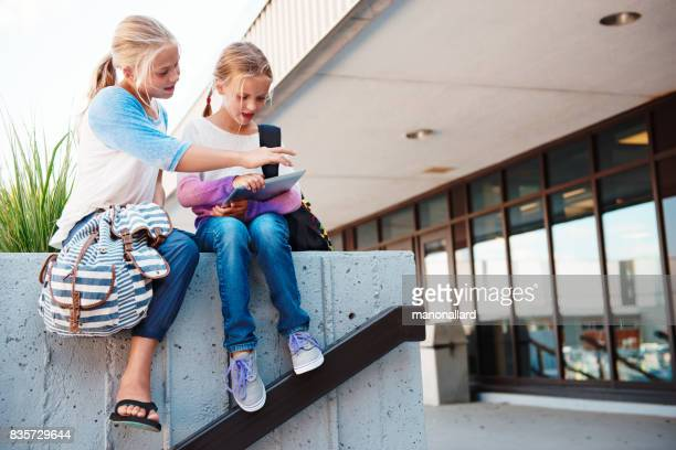 Two young students girls back to school working on digital tablet at the entrance of the school