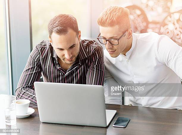 Two young successful businessmen working on laptop in meeting room