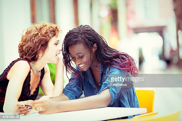 Two young talking mixed race girlfriends in sidewalk cafe