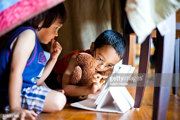 Two young toddlers viewing a tablet device inside their home.